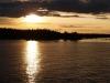 Ensam fiskare puttrar runt i solnedgången, vid Gållsgrund norr om Gävle.